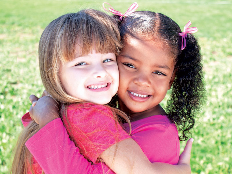 Two young girl friends hugging and smiling.